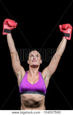 Winner female boxer with arms raised against black background