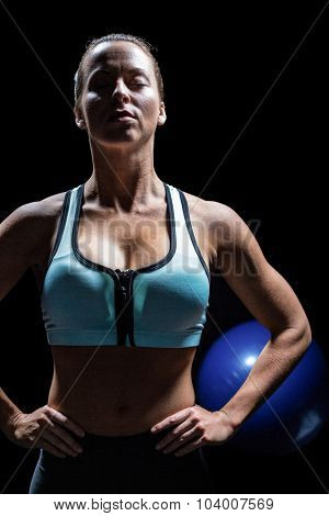 Fit woman relaxing with hands on hip against black background