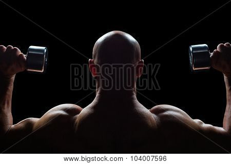 Rear view of man exercising with dumbbells against black background