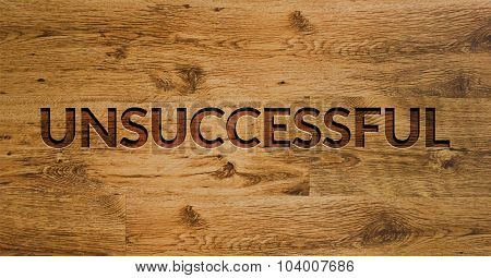 The word UNSUCCESSFUL Engraved in Wooden Background