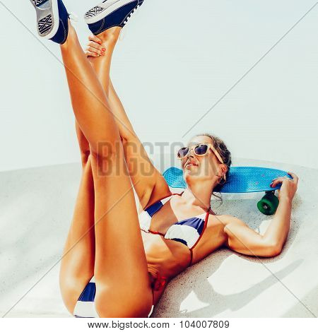 Sexy Suntanned Lady Sitting With Blue Penny Board On The Beach
