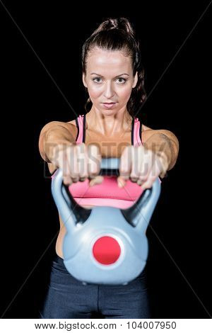 Portrait of fit woman lifting kettlebell against black background