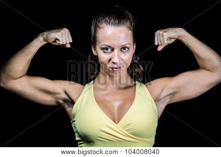 Portrait of confident athlete flexing muscles against black background