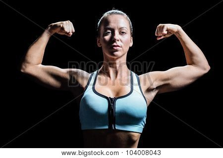 Thoughtful athlete flexing muscles against black background