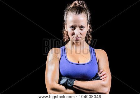Portrait of sporty woman with arms crossed against black background