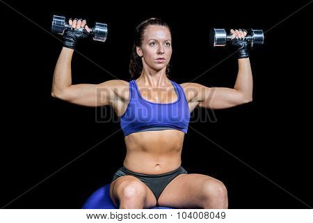 Confident woman lifting dumbbells while sitting on ball against black background