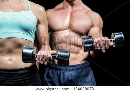 Midsection of woman and man exercising with dumbbells against black background