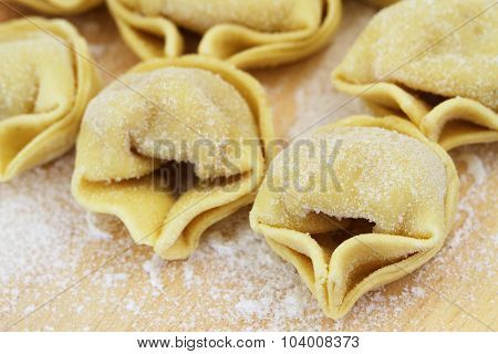 Uncooked tortellini on wooden board, closeup