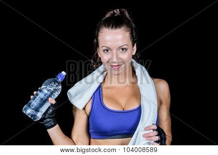 Portrait of pretty smiling woman with water bottle against black background