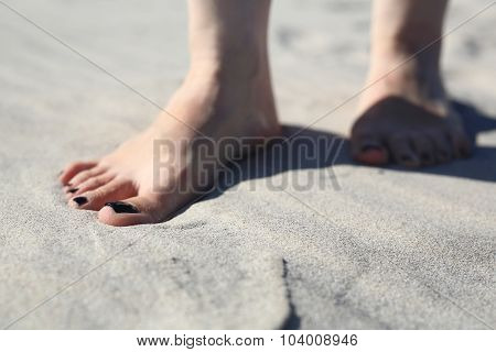Feet of a woman buried in sand on the beach