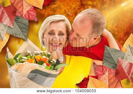 Mature man kissing his partner holding flowers against autumn scene