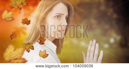 Depressed businesswoman looking away against autumn scene