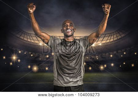 Happy sportsman with clenched fist after victory against large football stadium under night sky