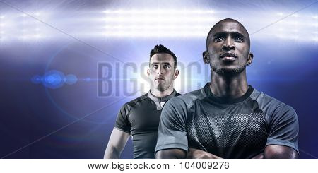 Thoughtful athlete standing with arms crossed against spotlights