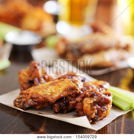 pile of barbecue buffalo chicken wings on wax paper served with celery