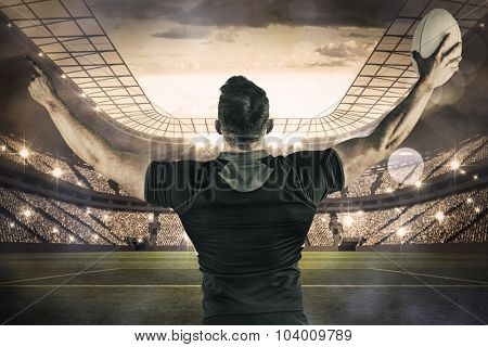 Rugby player celebrating with the ball against large football stadium with lights