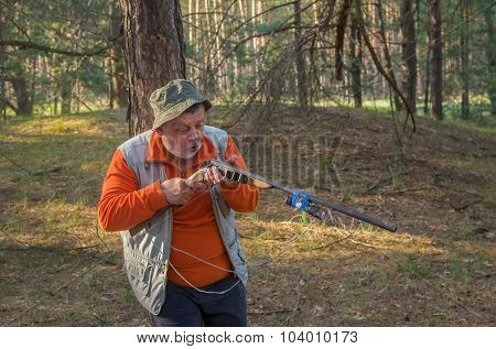 Outdoor portrait of senior hunter examining of hunting rifle