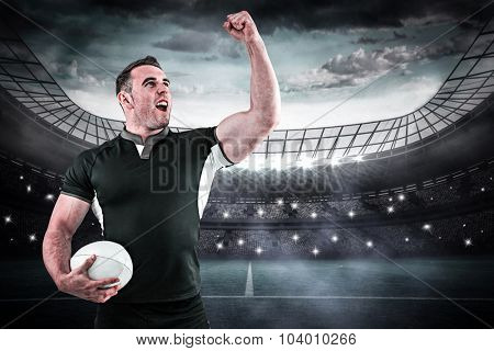 Rugby player cheering with the ball against large football stadium under blue sky
