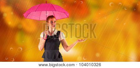 Pretty redhead businesswoman holding umbrella against autumn scene