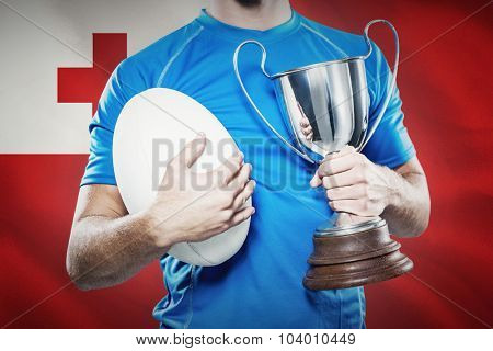 Rugby player holding trophy and ball against close-up of tongan flag