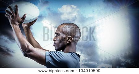 Athlete in position of throwing rugby ball against spotlight in sky