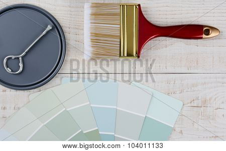 Painting still life with brush, paint chips, paint can lid with opener on a rustic wood surface. Horizontal format.