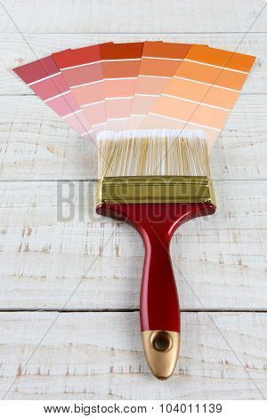 Overhead vertical shot of  a paint brush and different shades of color samples on a rustic white wooden surface.