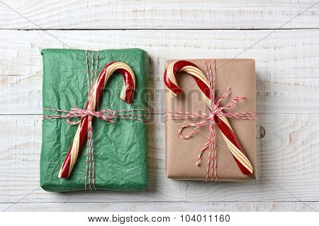 Two Wrapped Christmas presents tied with string and topped with large old fashioned candy canes, Horizontal format. Gifts are wrapped with plain paper one brown one green.