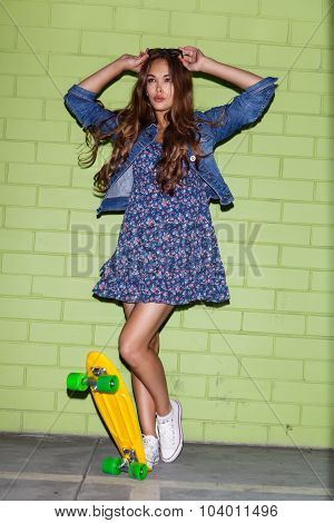 Beautiful Long-haired Lady With A Yellow Penny Skateboard Near A Green Brick Wall
