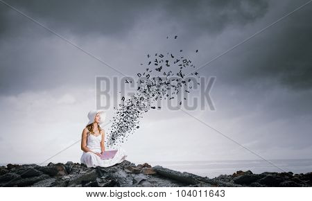 Young lady sitting on top of mountain with laptop
