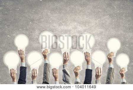 Many human hands holding light bulb signs