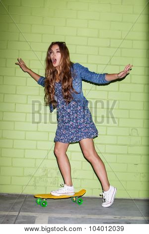 Beautiful Long-haired Girl With A Plastic Penny-board Near A Green Brick Wall
