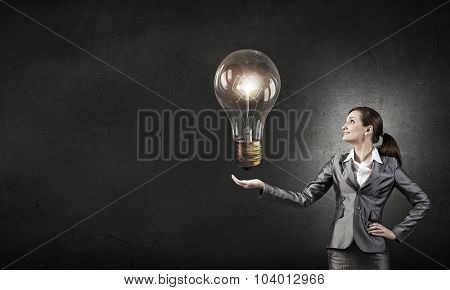 Young businesswoman presenting glass glowing light bulb in her hand