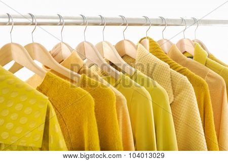 Variety of female yellow clothing on hanging