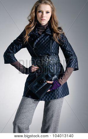 fashion model in modern clothes holding handbag posing