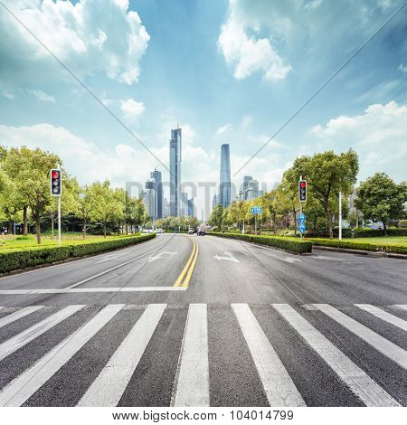 empty road with zebra crossing and skyscrapers in modern city