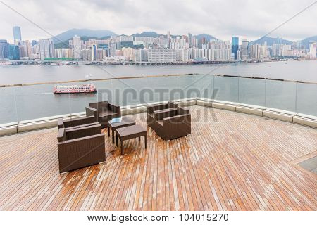 tea table and chairs besides the river around a city