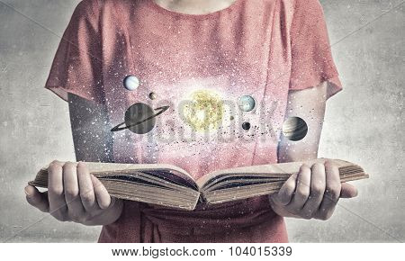 Close up of woman with book exploring planets of sun system