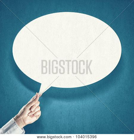 Hand holding an empty speech bubble on blue background