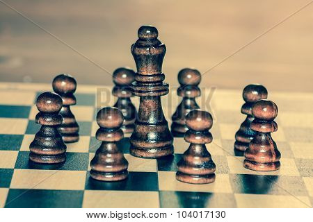 Team of wooden chess pawns and chess queen.