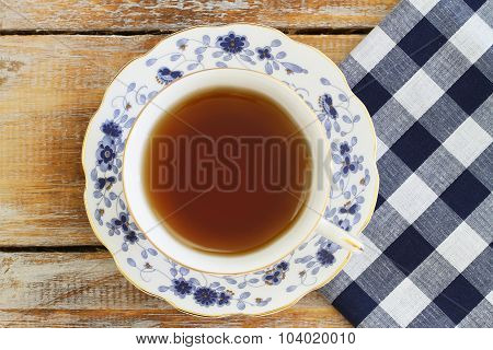 Cup of black tea in vintage porcelain cup on rustic wooden surface