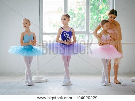 Three little ballerinas with personal ballet teacher in dance studio