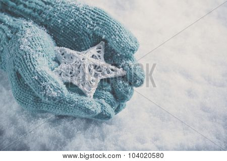 Female hands in light teal knitted mittens with entwined white star on a white snow background. Winter and Christmas concept.