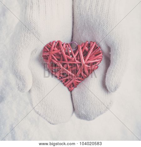 Female hands in white knitted mittens with a entwined vintage romantic red heart on a snow winter background. Love and St. Valentine concept.