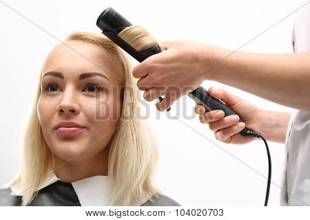 A woman in a hair salon, barber turns hair curling iron