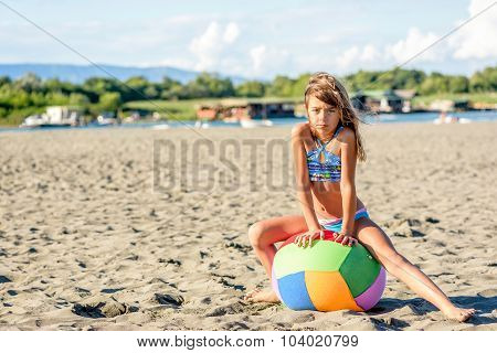 Beautiful Eight Year Old Girl Playing With The Ball On The Beach