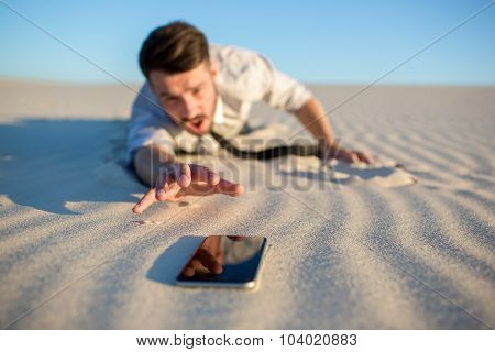 Poor signal. businessman searching for mobile phone signal in desert