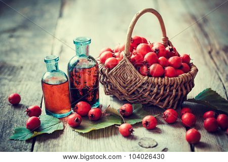 Tincture Bottles Of Hawthorn Berries And Ripe Thorn Apples In Basket On Old Wooden Table. Herbal Med