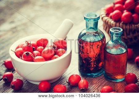 Mortar Of Hawthorn Berries, Two Tincture Bottles And Thorn Apples In Basket On Old Wooden Table. Her