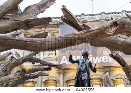 LONDON, UK - SEPTEMBER 23: Statue of Sir Joshua Reynolds framed by branches of Ai Wei Wei's installation 'Tree' in the forecourt of the Royal Academy of Arts. September 23, 2015 in London.